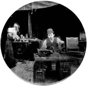 Charles Kayser of the Edison lab seated behind the Kinetograph. Portability was not among the camera's virtues. Via Wikipedia.