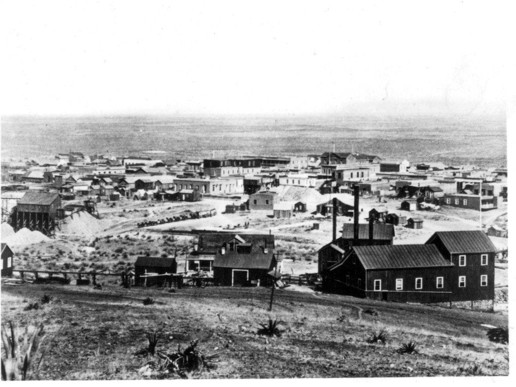Tombstone, Arizona in 1881 photographed by C. S. Fly. An ore wagon at the center of the image is pulled by 15 or 16 mules leaving town for one of the mines or on the way to a mill. The town had a population of about 4,000 that year with 600 dwellings and two church buildings. There were 650 men working in the nearby mines. The Tough Nut hoisting works are in the right foreground. The firehouse is behind the ore wagons, with the Russ House hotel just to the left of it. The dark, tall building above the Russ House is the Grand Hotel, and the top of Schieffelin Hall (1881) is visible to the right.